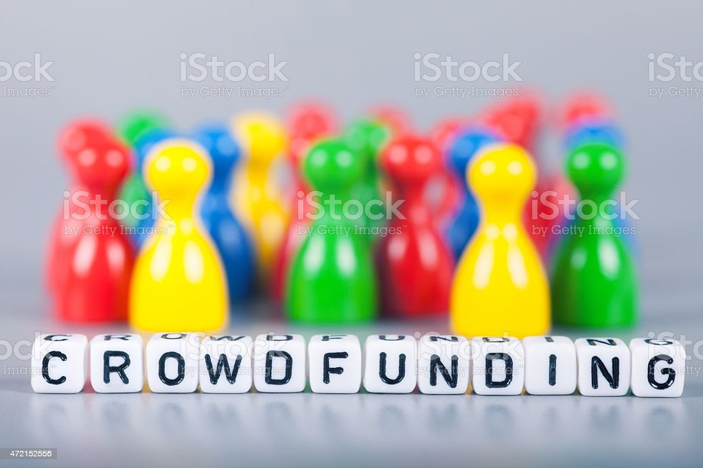 Cube Letters show crowdfunding  in front of unsharp ludo figures stock photo