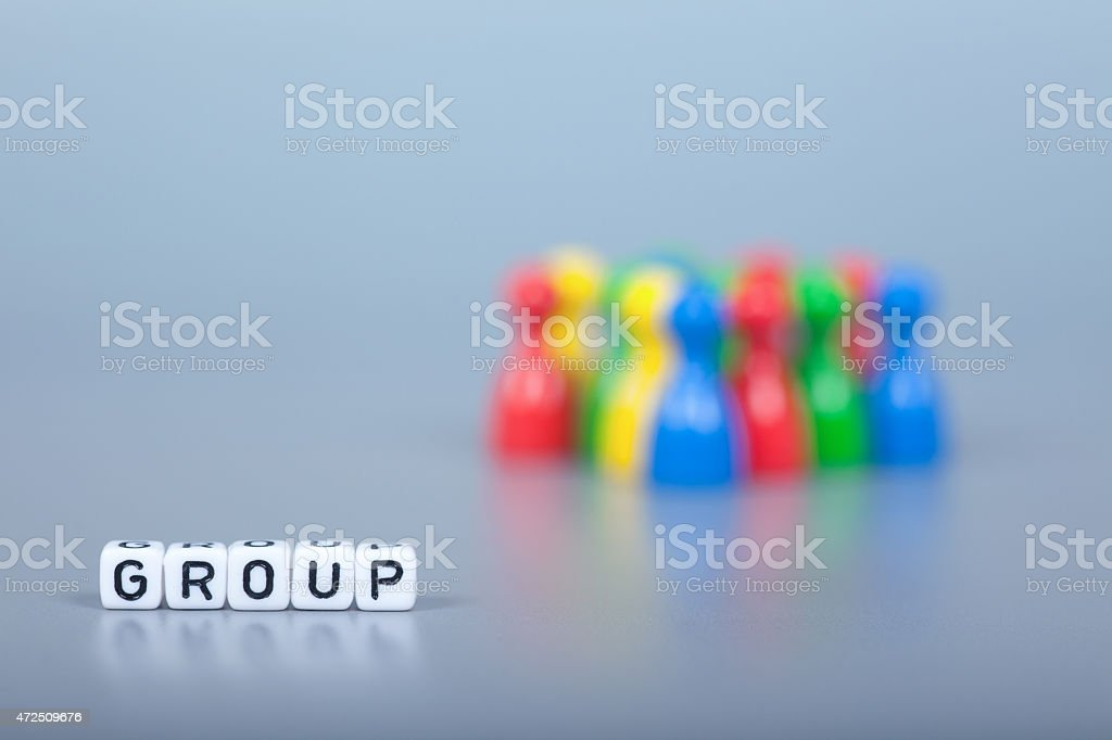 Cube Letters show Group  in front of unsharp ludo figures stock photo