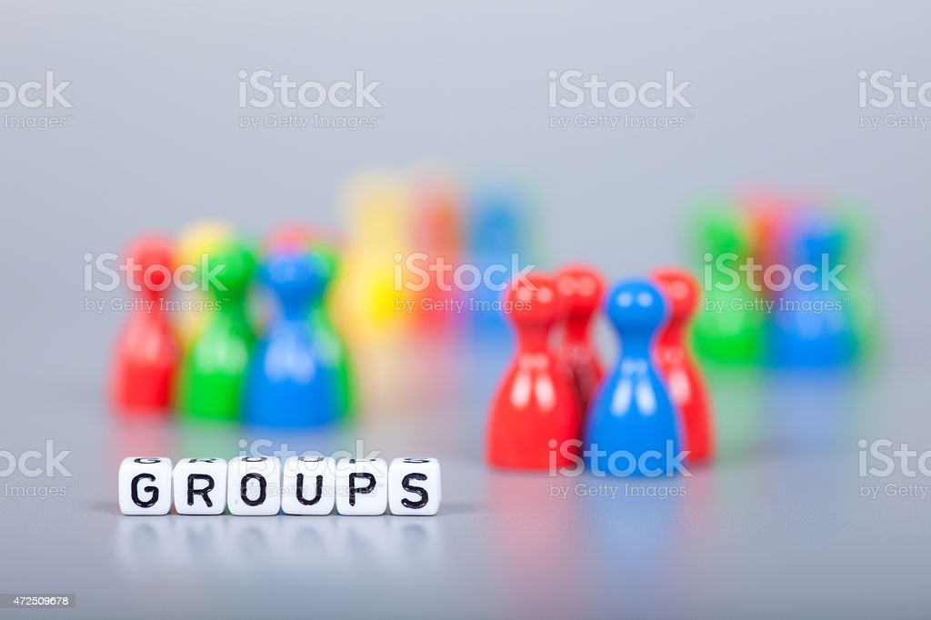 Cube Letters show Groups  in front of unsharp ludo figures stock photo