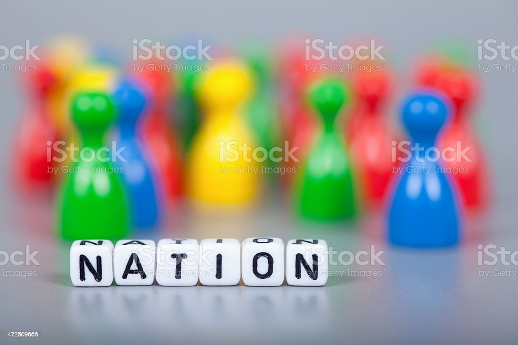 Cube Letters show nation  in front of unsharp ludo figures stock photo