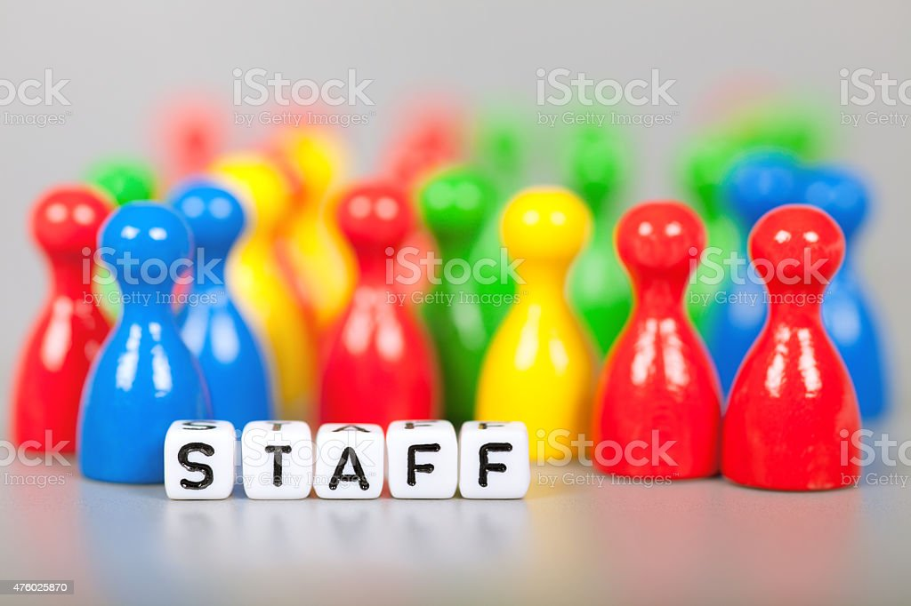 Cube Letters show staff  in front of unsharp ludo figures stock photo