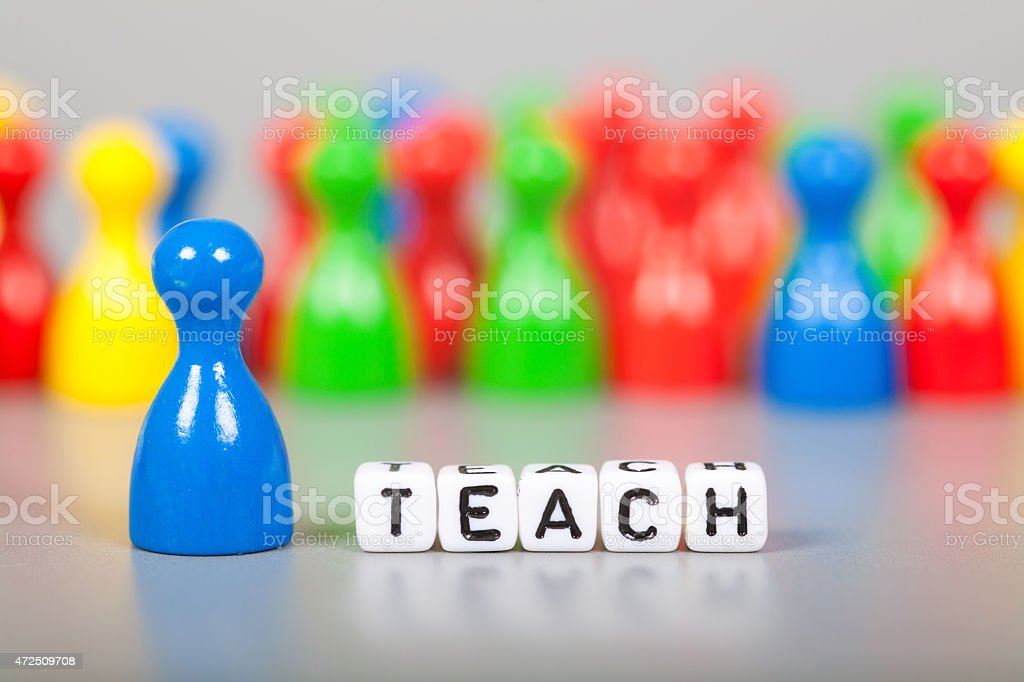 Cube Letters show teach  in front of unsharp ludo figures stock photo
