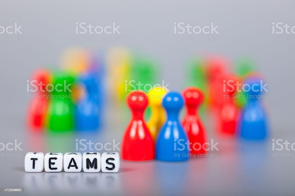 Cube Letters show teams  in front of unsharp ludo figures stock photo