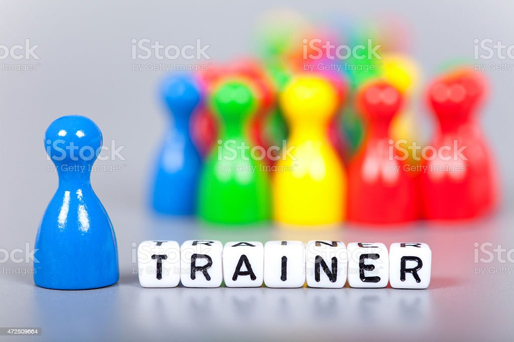 Cube Letters show trainer  in front of unsharp ludo figures stock photo