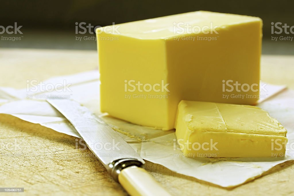 A cube of butter sliced with a knife  stock photo