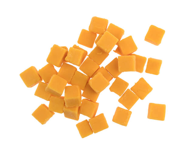 cubed mild cheddar cheese on a white background - cube shape stock pictures, royalty-free photos & images