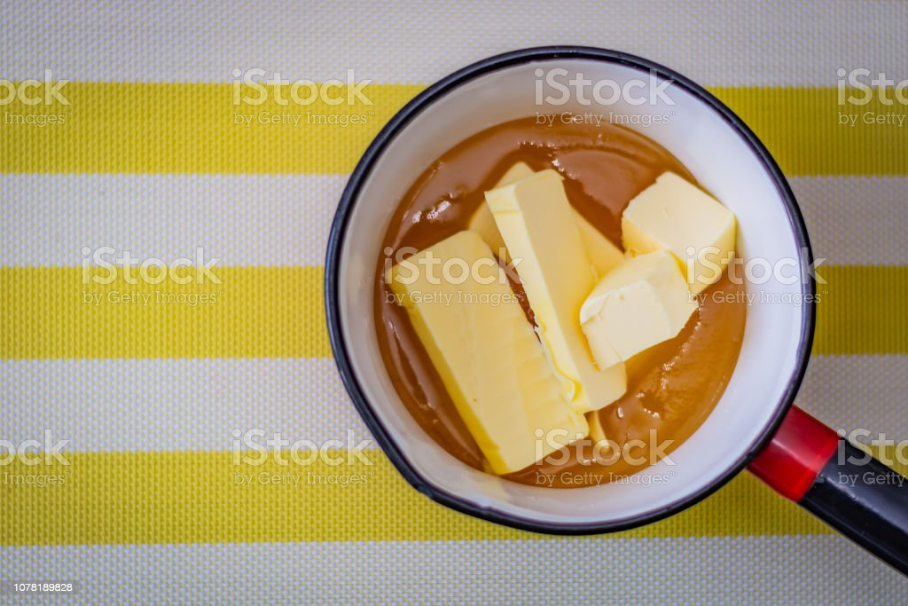 Cubes of butter embedded in honey in a saucepan ready to be heated for baking – zdjęcie