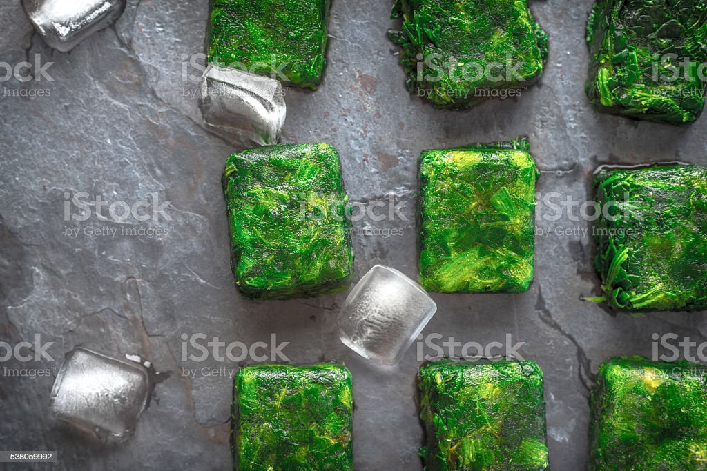 Cubes of frozen spinach with ice cubes on stone table – Foto