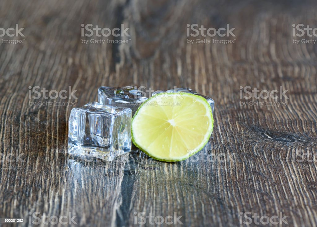 Cubes of ice and slice of lime in a wooden table royalty-free stock photo