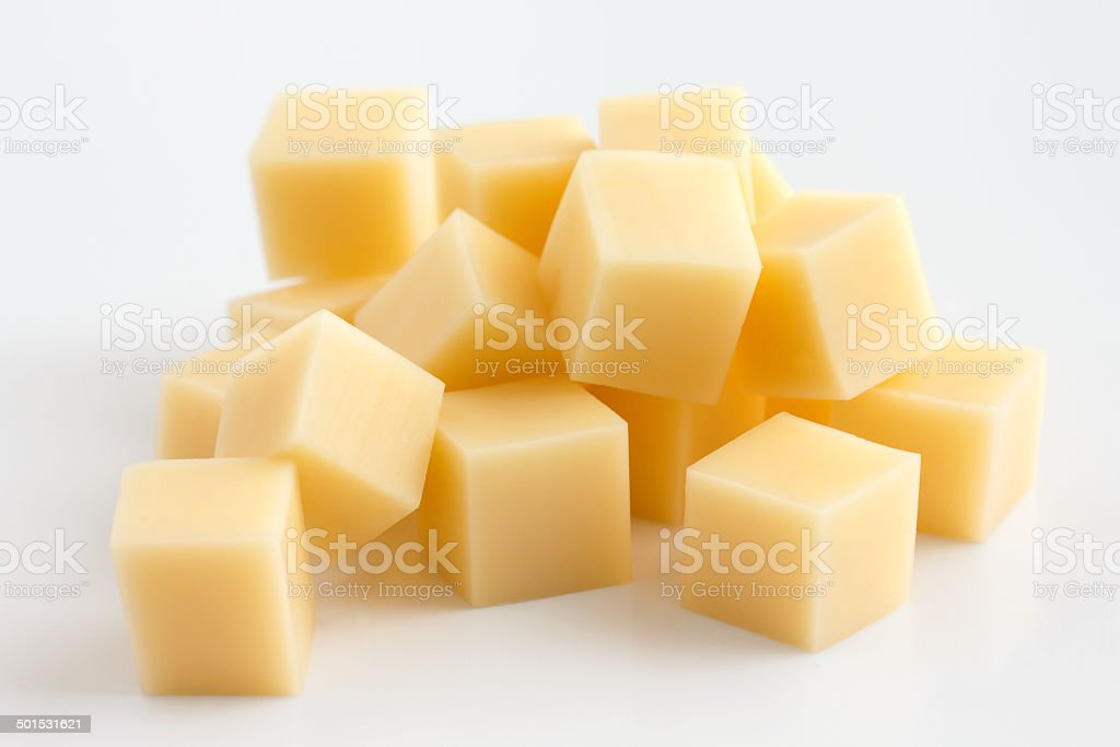 Cubes of yellow cheese stacked randomly on white. stock photo