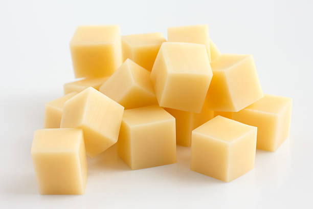cubes of yellow cheese stacked randomly on white. - cube shape stock pictures, royalty-free photos & images