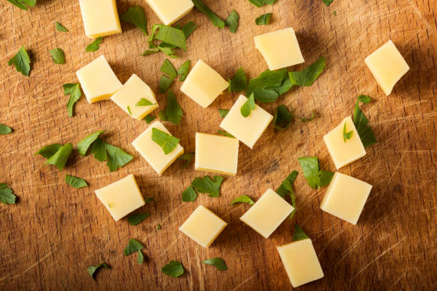 Cubes of yellow cheese stacked randomly stock photo