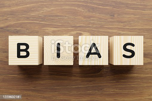 Bias - word on wooden cubes. Cubes with letters form the word bias. Wooden cubes with different textures, top view.