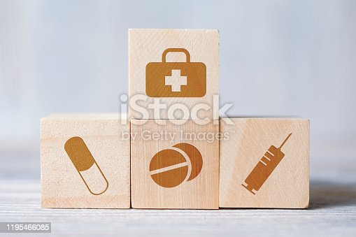 istock Cubes with medical icons of doctor's bag, pills, syringe on wooden background. 1195466085