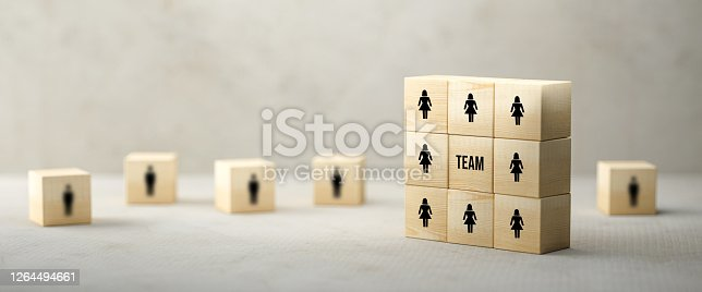 cubes with people symbols and the word TEAM on paper surface in front of concrete background - 3d illustration