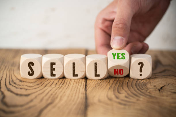 "cubes with the word ""SELL"" and hand turning a cube with answer ""yes"" and ""no"" stock photo"