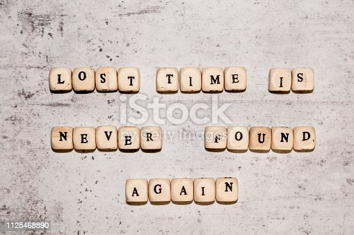istock Cubes with the words LOST TIME IS NEVER FOUND AGAIN on a gray concrete background. Top view Selective focus. 1125468890