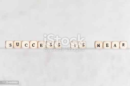 istock Cubes with the words SUCCESS IS NEAR on a gray concrete background. Selective focus. 1125468885