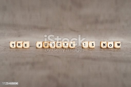 istock Cubes with the words THE FUTURE IS NOW on a gray concrete background. Selective focus. 1125468896