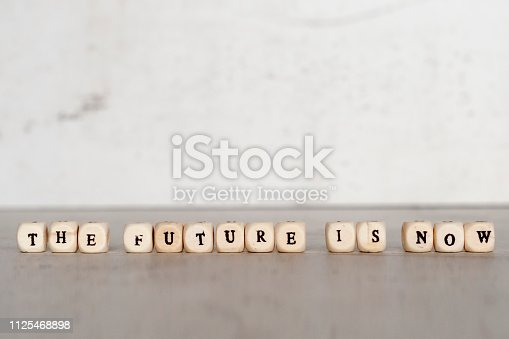istock Cubes with the words THE FUTURE IS NOW on a gray concrete background. Selective focus. 1125468898