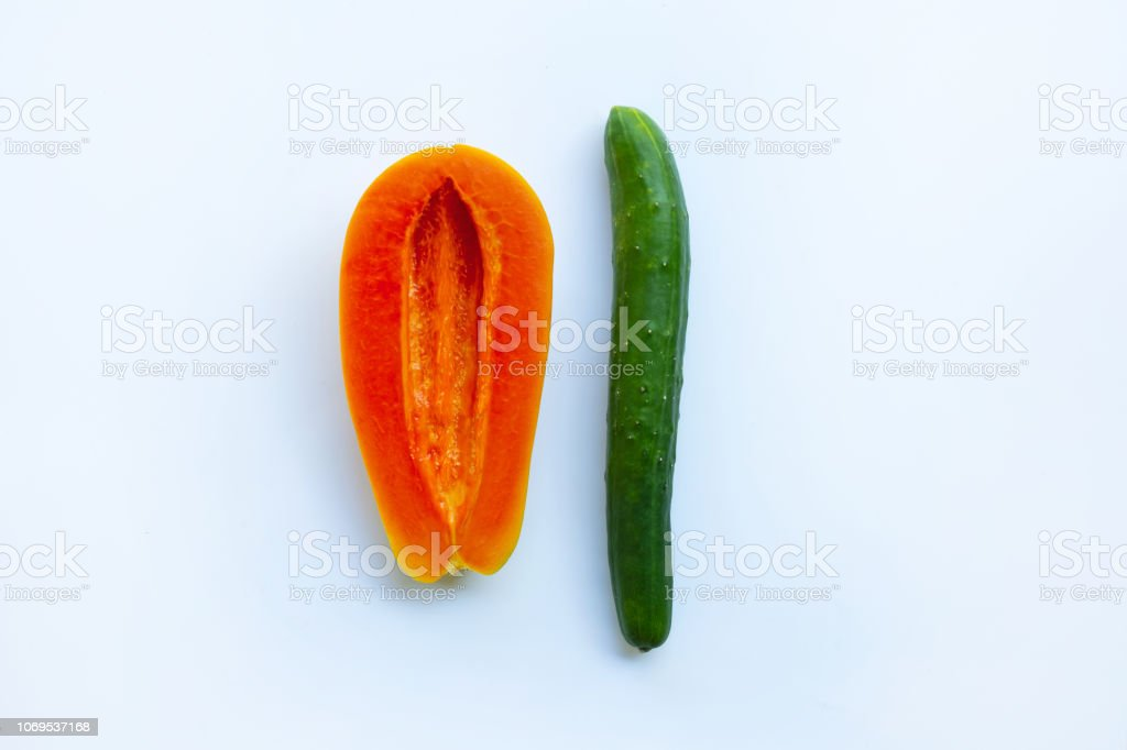 Cucumber and papaya  on white background. Sex concept. Cucumber and papaya  on white background. Sex concept. Banana Stock Photo