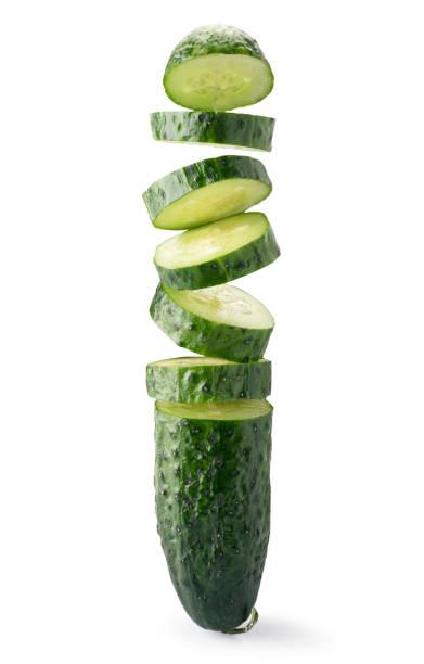 komkommer gesneden in stukjes vliegen in de lucht close-up op een witte achtergrond. geïsoleerd. - komkommer stockfoto's en -beelden