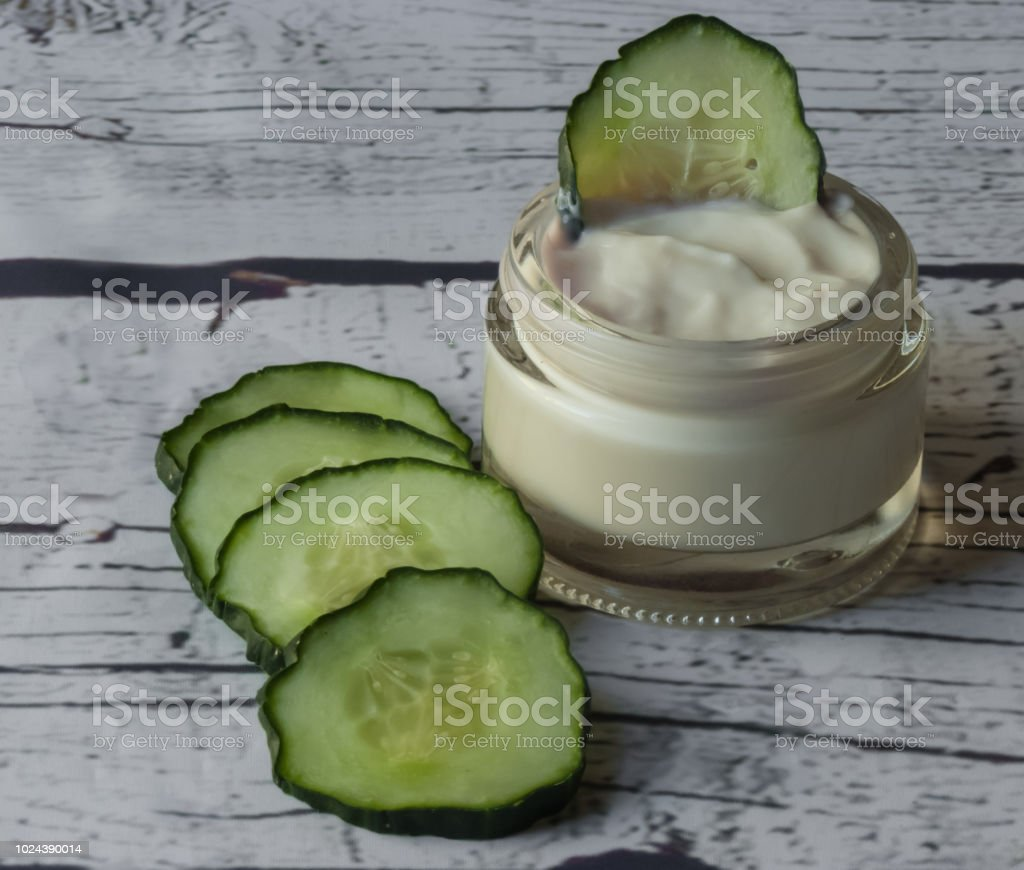 Cucumber face cream on white wooden background stock photo