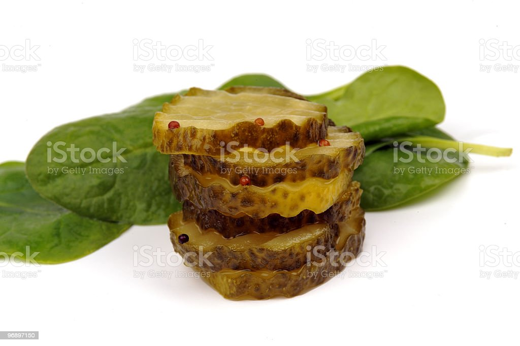 Cucumber pickles with mustard seed and spinach leaves royalty-free stock photo