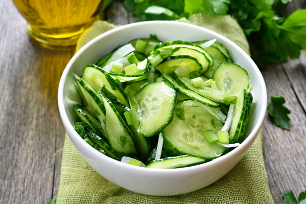 cucumber salad in white bowl - komkommer stockfoto's en -beelden