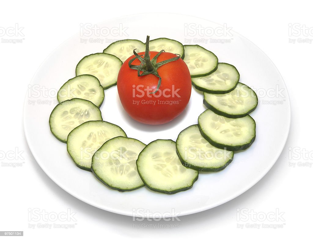 Cucumber slices and tomato on white plate royalty-free stock photo