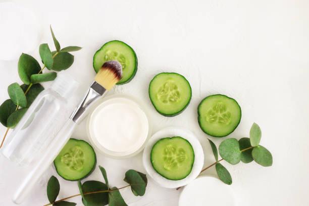gurkenscheiben, kosmetische creme jar und stärkungsmittel mineralwasser in der flasche, frische grüne eukalyptus-blätter, oben weißen hintergrund betrachtet. - gurkenmaske stock-fotos und bilder
