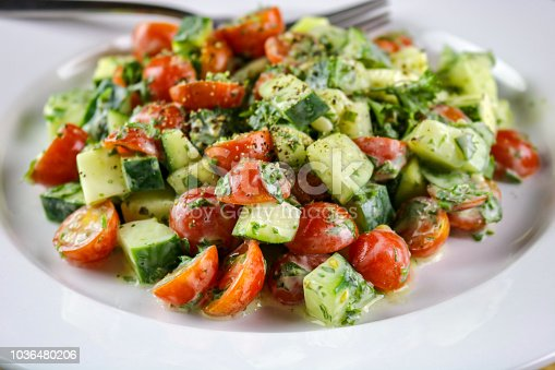 A freshly made cucumber, tomato and herb salad with a creamy vinaigrette dressing