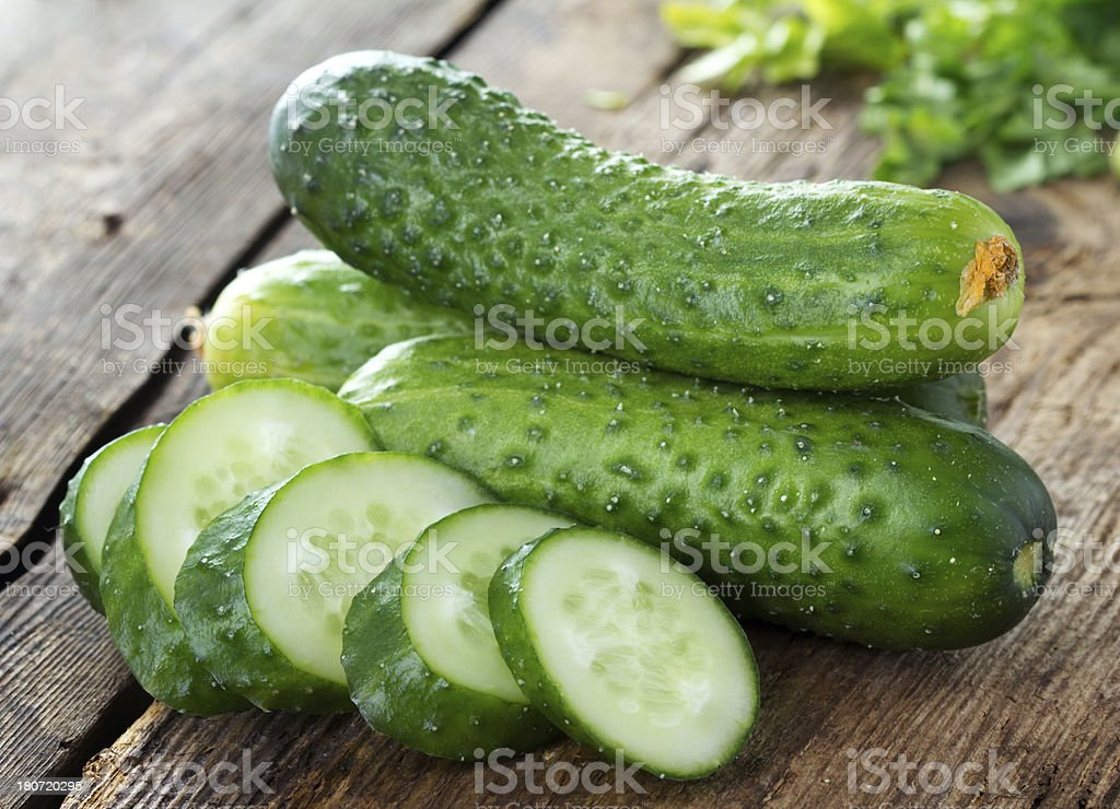 Cucumbers and slices on wooden table stock photo
