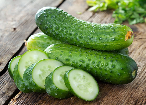 cucumbers and slices on wooden table - komkommer stockfoto's en -beelden