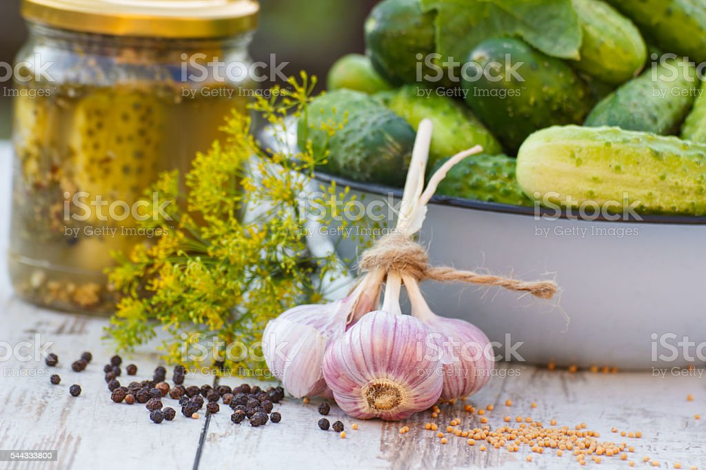 Cucumbers in metal bowl, spices for pickling, jar pickled cucumbers stock photo
