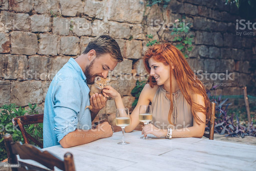 Young couple drinking wine on balcony at restaurant. Cuddling little...