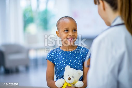 A beautiful little girl smiles as she holds her teddy bear like a baby. Her doctor is facing her. She is battling cancer.