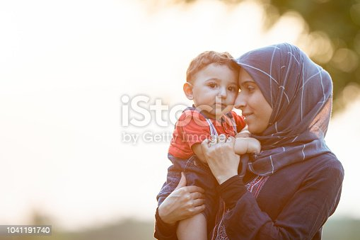 A mother and young son are outdoors on a sunny day. The mother is lovingly holding her son in her arms.