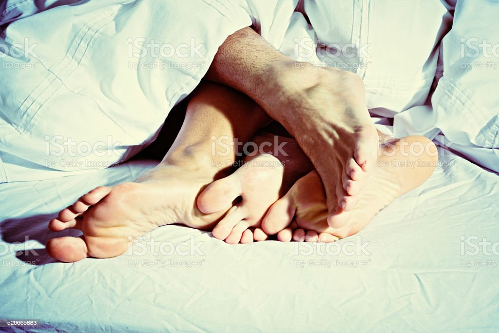 Cuddling up under the covers; four bare feet in bed stock photo