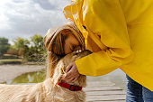 Photo of young woman and her dog enjoying together on the dock