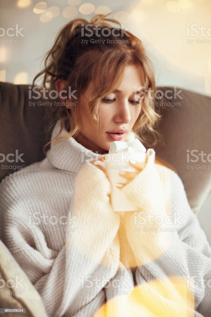 Cuddling woman with cacao in armchair zbiór zdjęć royalty-free