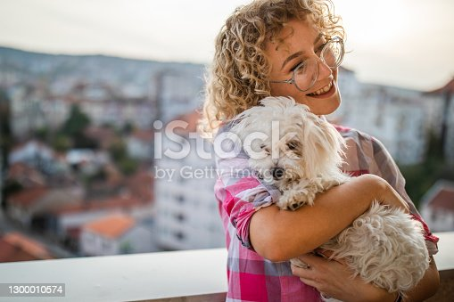 Young woman hugging her white puppy on the balcony. Sun is setting behind them.