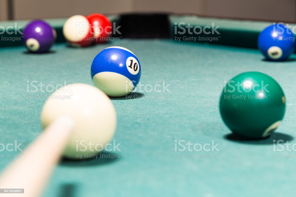 Cue aiming red ball into snooker billards table pocket stock photo