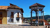 Cuenca, Ecuador - February 5, 2020: Historical center of city Cuenca, one of the oldest district of city, UNESCO heritage site. View at the street De La Cruz with colonial architecture and religion monument Cruz del Vado, installed in 1557 year