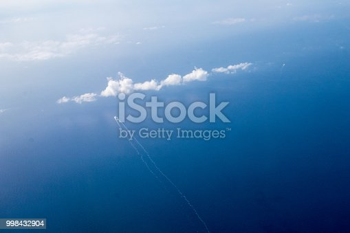Cuise ship seen from the plane in the mediterranean. Ship in the open sea that leaves behind it, a cloud on the left.