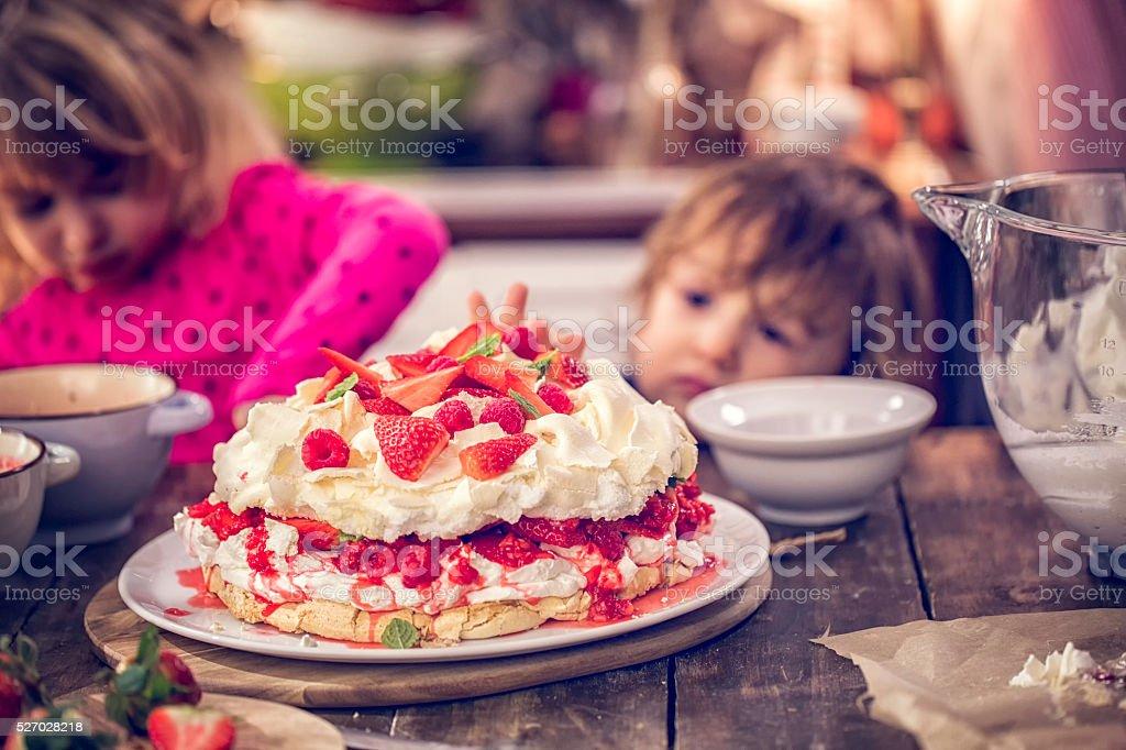 Cule Kids Eating Berry Pavlova Cake with Strawberries and Raspberries stock photo
