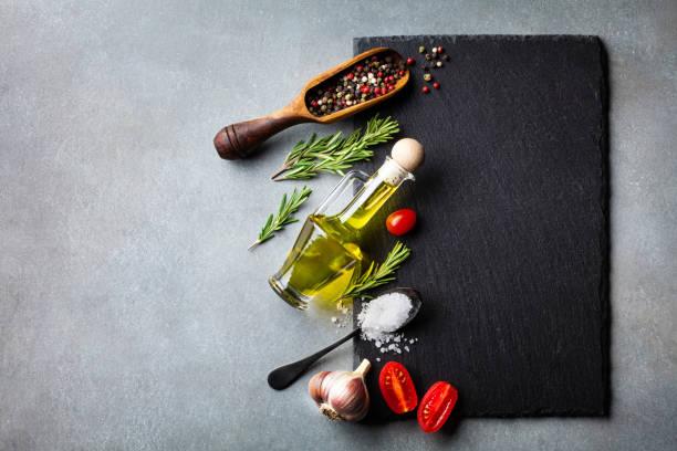 kulinarischer hintergrund mit küchenschieferbrett, kräutern und verschiedenen gewürzen. leerer platz für menü oder rezept. ansicht von oben. - gourmet küche stock-fotos und bilder