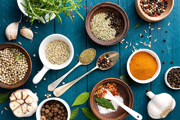 culinary background with spices on wooden table - herb stock photos and pictures