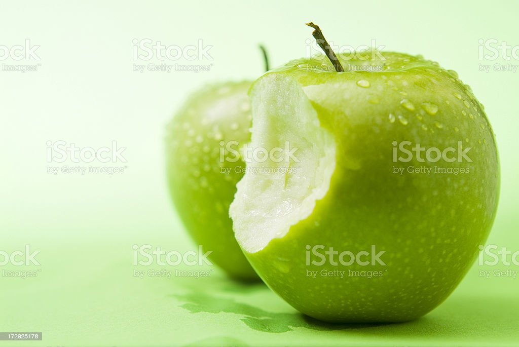 Culinary image of a green apple with a bite out of it royalty-free stock photo
