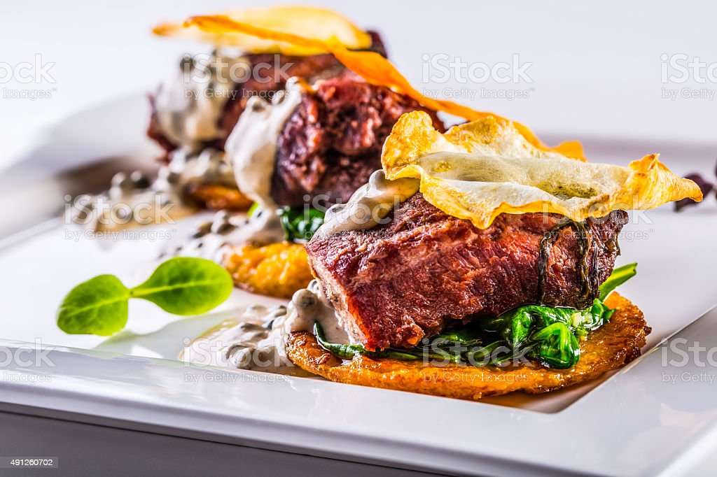 Culinary kitchen. Confit pork cheeks with green spinach leaves stock photo